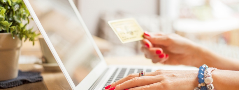 Female hand on laptop and holding credit card while online shopping