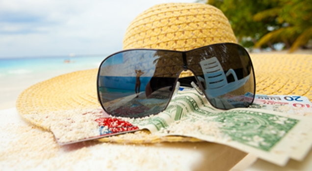 straw hat on beach with sunglasses atop sandy money